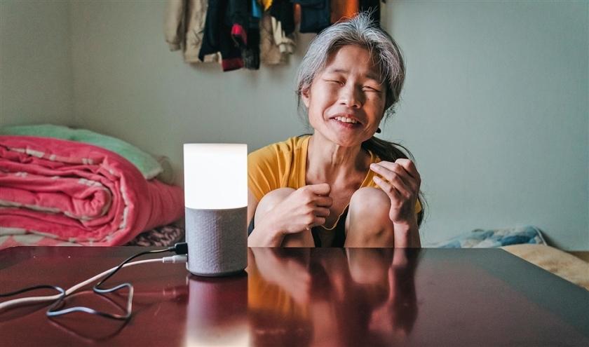 De bijna volledig blinde Jang Ae-ja (55) met de slimme speaker in haar huis in Seoul.  (Jun Michael Park)