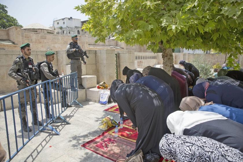 Palestijnen bidden dinsdag bij de Leeuwenpoort in Jeruzalem. Ze reageren op een oproep van geestelijken om niet in de moskee, maar hier te bidden.  (ap / Oded Balilty)