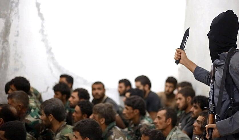 Een strijder van ISIS, gewapend met een mes en een automatisch wapen, bewaakt Syrische soldaten die worden gebruikt als menselijk schild.  (ap)