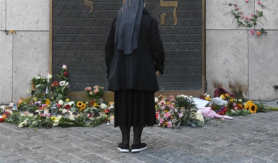 Een zuster gedenkt bij de ingang van de synagoge in de Duitse stad Halle de slachtoffers, een paar dagen na de aanslag.  (afp / Christoph Stache)
