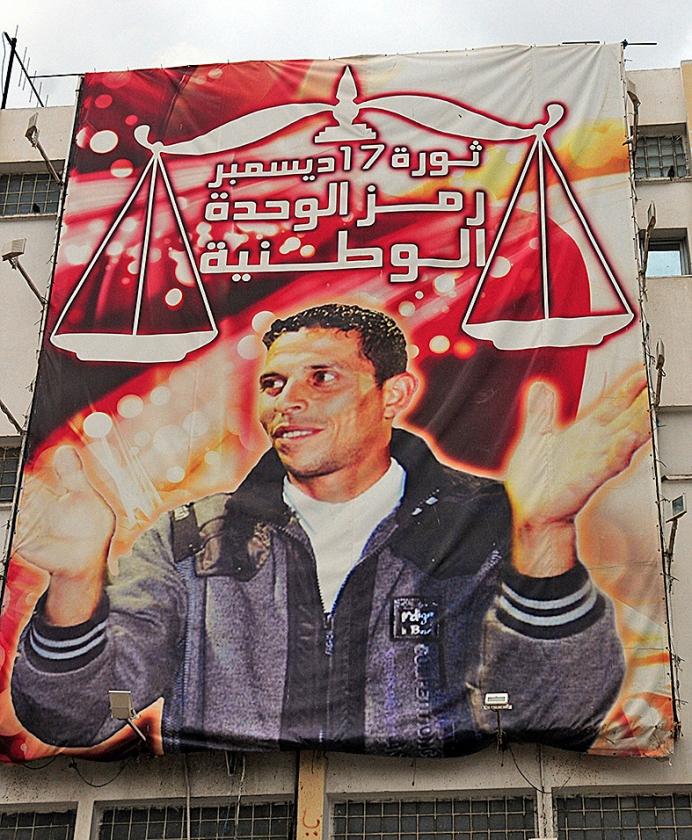 Een poster met de fruitverkoper Mohamed Bouazizi in Sidi Bouzid, Tunesië, die zichzelf in brand stak uit protest tegen een corrupte politie.   (ap)