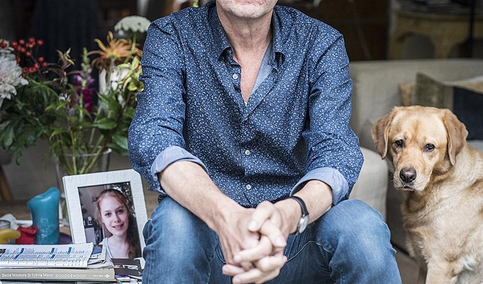 Koos Neuvel met een foto van zijn dochter Nora en met labrador Luna, die het gezin ooit in huis haalde voor Nora.   (Linelle Deunk)