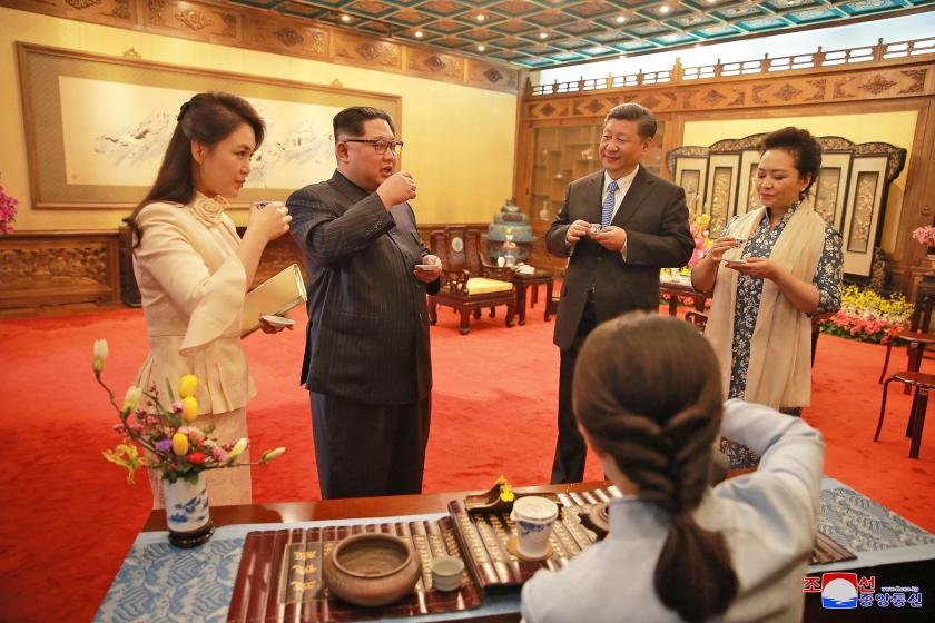 De Noord-Koreaanse leider Kim Jong-un en zijn vrouw (links) drinken thee met president Xi Jinping van China en diens echtgenote, woensdag in Peking.