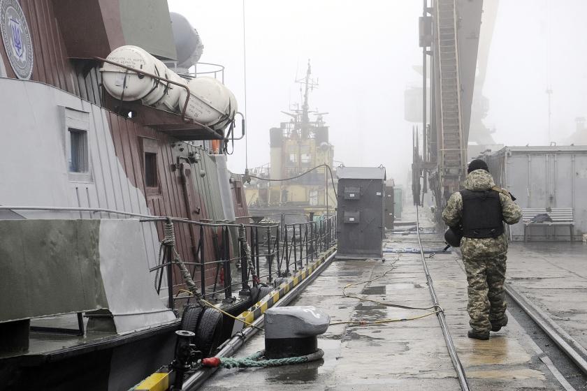 Een Oekraïense militair patrouilleert op de kade van de haven van Marioepol. De havenarbeiders zelf vervelen zich stierlijk nu de schepen de Zee van Azov niet uit kunnen.  (afp / Aleksey Filippov)