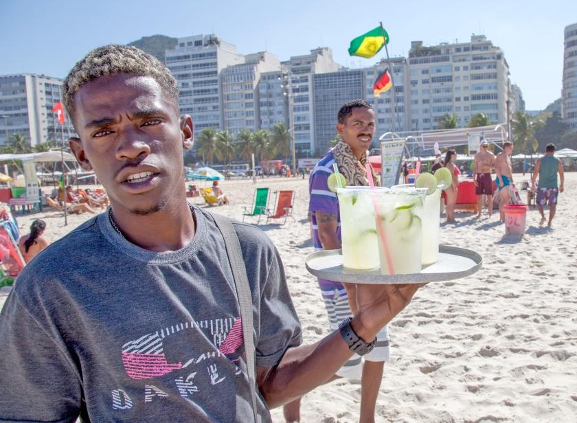 Een strandverkoper op Copacabana, met de populaire cocktail caipirinha. Achter het zonnige imago van Rio de Janeiro gaan veel problemen schuil.  (ap / Herbert Knosowski)