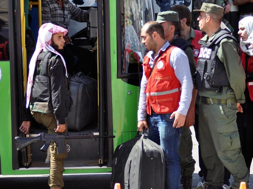 Niet alleen bewoners worden per bus uit heroverde wijken gereden, ook militairen van Assad stappen in om na de overwinning verder te trekken.  (ap)
