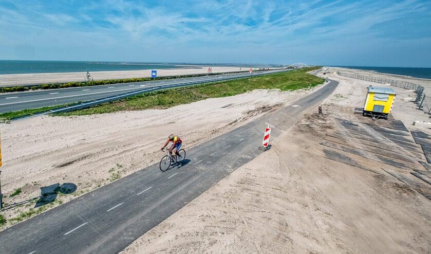 Een eenzame fietser ploegt over de dijk tussen de zandverstuivingen door.  (Raymond Rutting)