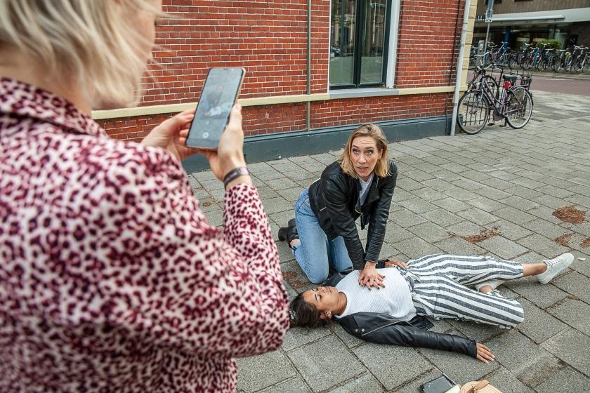 Eerstehulparts Heleen Lameijer (zittend) maakt met vrijwilligers korte Instagramfilmpjes over hoe je iemand kunt reanimeren.  (Harry Cock)