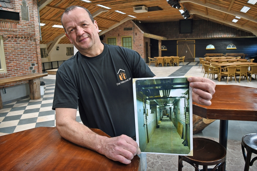 Wim Luijten in zijn voormalige varkensstal met een foto van vroeger.  (Marcel van den Bergh)