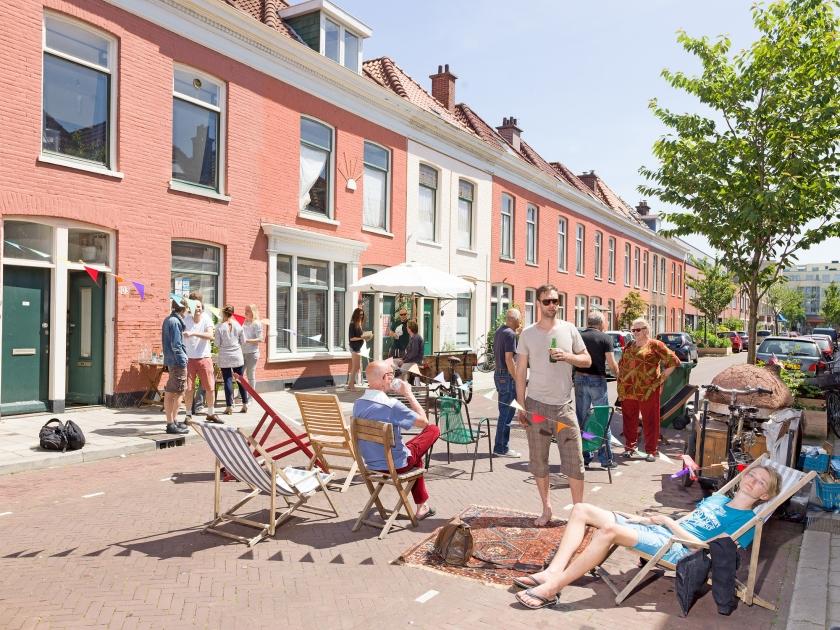 Bewoners van de Roggeveenstraat in Den Haag genieten samen van de zon. Hun coöperatie wordt eigenaar van de huurwoningen.  (Ivo van der Bent)