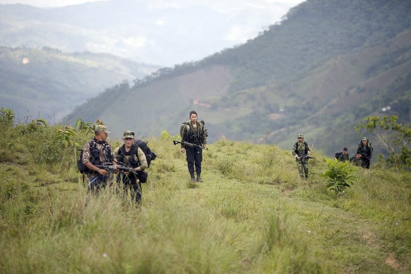 FARC-rebellen in het bergland van Colombia. Bewoners in regio's waar de guerrilla's heersen, zien de strijders liever niet vertrekken. Nu weten ze waaraan ze toe zijn en ze vrezen dat paramilitaire groepen hun plaats innemen.  (ap / Rodrigo Abd en Desmond Boylan)