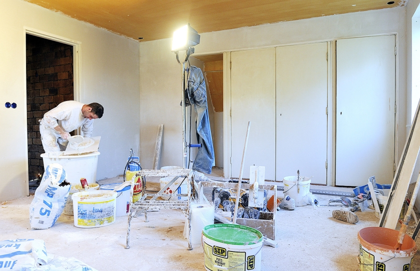 Een stukadoor aan het werk in een woning die gerenoveerd wordt. Dat is zwaar werk, maar stukadoors moeten nu nog net zo lang doorwerken voor ze aan hun AOW toe zijn als mensen die lichtere werkzaamheden verrichten.  (anp / Lex van Lieshout)