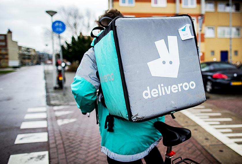 Deliveroo-bezorger op pad met een maaltijd in zijn rugzakbox.  (anp / Remko de Waal)