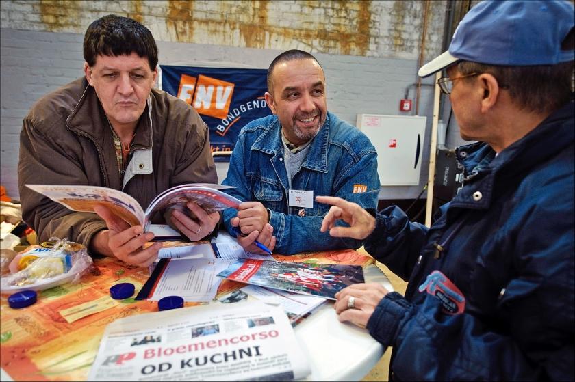 Een medewerker van de FNV (m) in gesprek met Poolse arbeiders op de Poolse Banenbeurs in de Westergasfabriek in Amsterdam.  (anp / Erik van 't Woud)