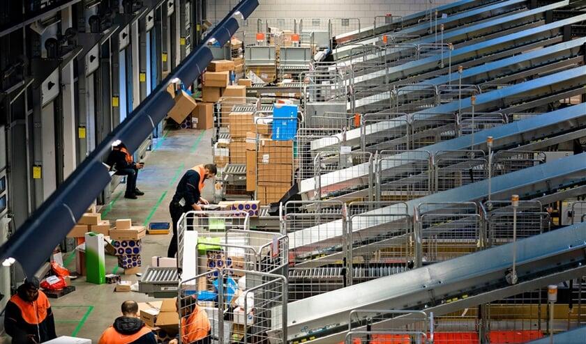 Het PostNL-sorteercentrum in Sassenheim. In deze tijd van het jaar worden er dagelijks 1,5 miljoen pakketten verwerkt.  (Freek van den Bergh)