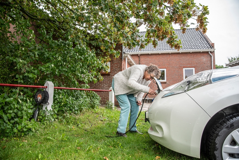 Rika Brik (74) stopt de stekker in een van de elektrische deelauto's in haar dorp. 'Laatst vroeg iemand of ik een keer met haar naar de Aldi wilde.'  (Harry Cock)