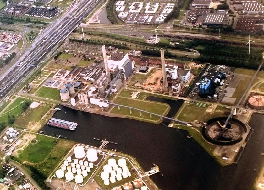 Een kolenopslag in de haven van Amsterdam met op de achtergrond een windmolen. In vijf jaar tijd is het aandeel van de klimaatonvriendelijke brandstof gestegen van 18 naar 29 procent.  (wikipedia)