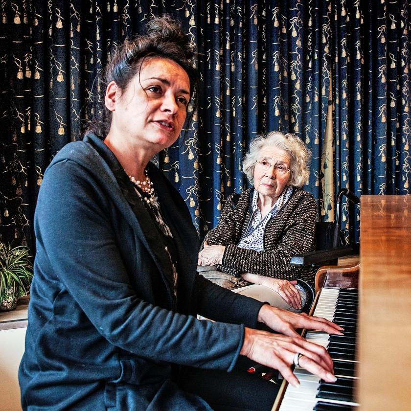 Begeleidster Brenda Frans speelt piano voor een cliënte.   (Ton Koene en Aurélie Geurts)