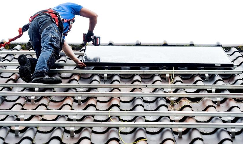 Een monteur plaatst zonnepanelen op het dak van een woonhuis. Aanbieders verwachten dat er dit jaar 7 miljoen panelen bijkomen.  (anp / Koen van Weel)