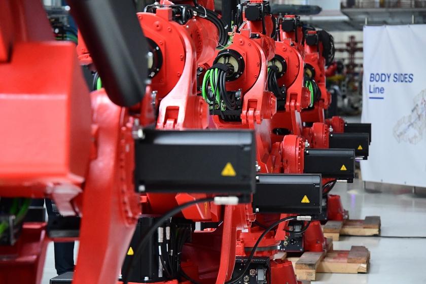 Een rij robots in de assemblagelijn van de elektrische Fiat 500 in de Fiat-fabriek in het Italiaanse Turijn. Door de opkomst van elektrische auto's raken traditionele auto-onderdelen uit de gratie, en dat gaat banen kosten.  (afp / Miguel Medina)