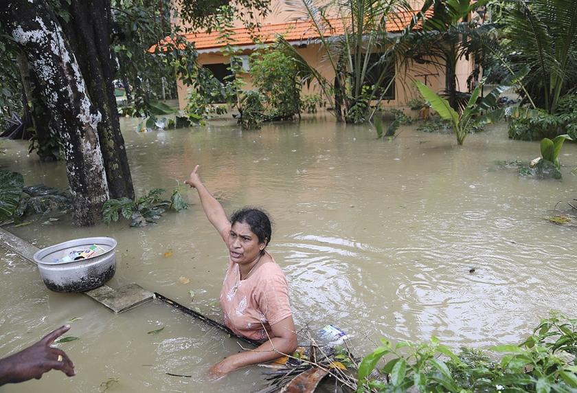 Een vrouw gebaart naar haar ondergelopen huis in de Indiase stad Chengannur terwijl ze hulpverleners vraagt om meer hulpgoederen.  (ap / Aijaz Rahi)