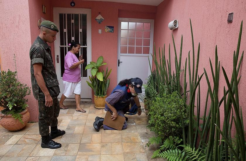 Een militair en een gezondheidswerker gaan de huizen langs op zoek naar stilstaand water.  (ap / Felipe Dana)