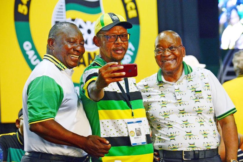 Een ANC-aanhanger maakt een foto van zichzelf tussen de nieuwe ANC-leider Cyril Ramaphosa (links) en zijn voorganger Jacob Zuma.  (ap)