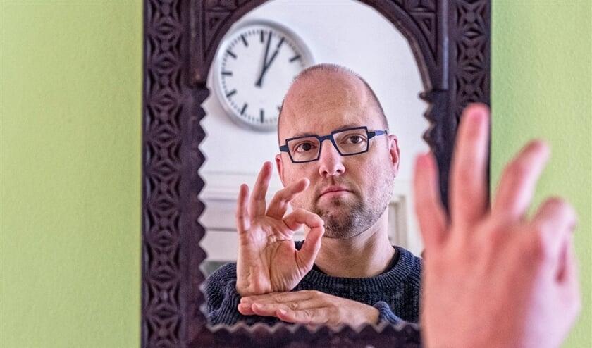 Hoogleraar gebarentaal Onno Crasborn maakt het gebaar voor 'les'.  (Raymond Rutting)