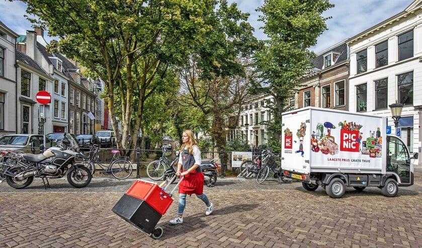 Een medewerker van onlinesupermarkt Picnic bezorgt boodschappen in Utrecht. De voertuigen van Picnic zijn al elektrisch.  (Raymond Rutting)