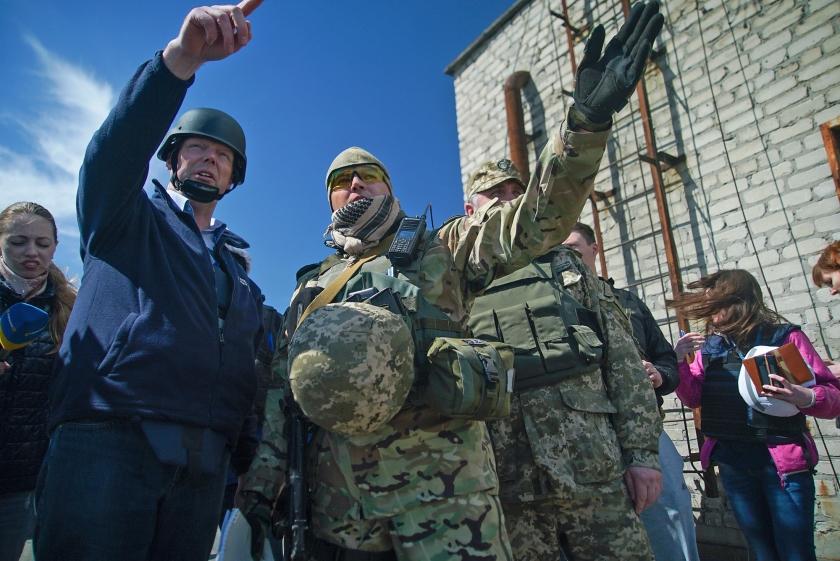 Alexander Hug aan de frontlinie, in gesprek met Oekraïense regeringsmilitairen.  (ap / Max Black)