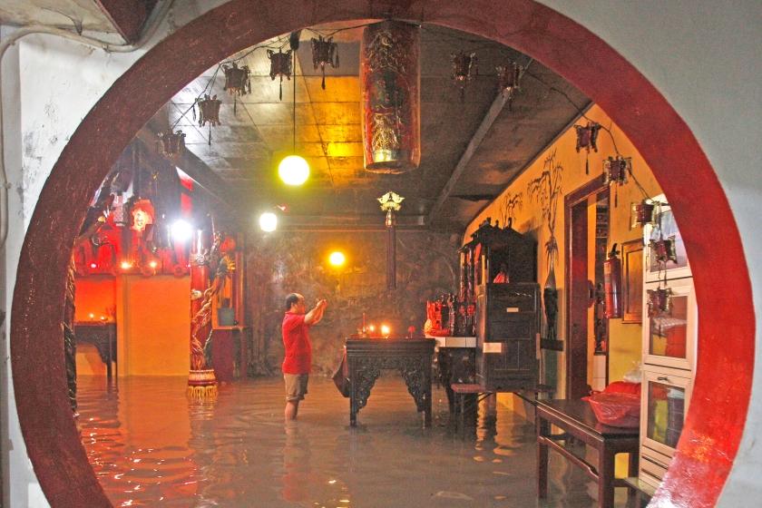 Een Chinese man die in Indonesië woonachtig is, bidt in een overstroomde tempel in Soerabaja, op Oost-Java. De afgelopen dagen heeft het in Indonesië hard geregend. De festiviteiten rond de viering van het Chinese nieuwjaar, dat op 8 februari begon, vielen daardoor soms letterlijk in het water.  (ap / Trisnadi)