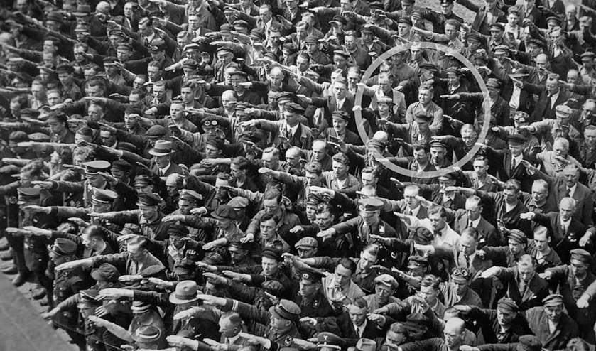 De massa in Hamburg salueert en brengt de Hitlergroet. Landmesser weigert en slaat de armen over elkaar.  (wikimedia)