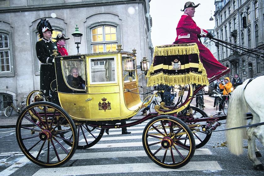 De Deense koningin Margrethe zit in haar Gouden Koets, op weg naar een nieuwjaarsbijeenkomst in Kopenhagen. De koets wordt ook wel 'De koets van Cristiaan VIII' genoemd. De coupé is met 24 karaat bladgoud bedekt en werd in 1840 door de Britse koetsbouwer Henry Fife gebouwd.  (ap / Philip Davali)