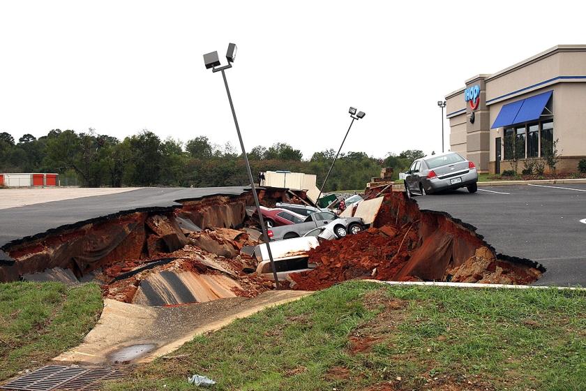 Auto's liggen over elkaar heen gebuiteld nadat een parkeerdek in de plaats Meridian, Mississippi (VS) zaterdag instortte. Deskundigen zoeken nog naar de oorzaak achter de breuk die een groot gat in het wegdek sloeg.  (ap /  Michael Stewart)