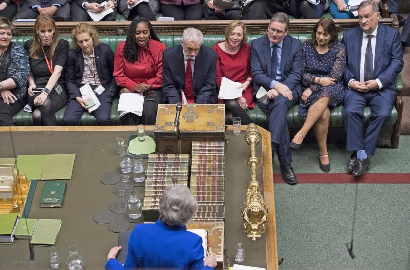 Theresa May en Jeremy Corbyn staan achter de versleten Despatch Boxes tegenover elkaar in het Britse parlement op woensdag 16 januari. De middentafel is maar een paar yards breed.  (afp / Jessica Taylor)