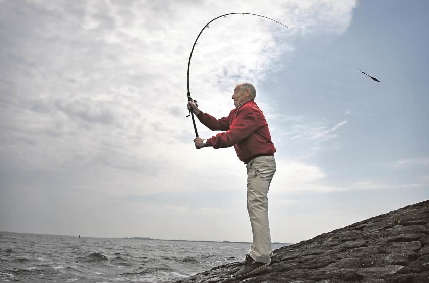 Een sportvisser gooit in de Oosterschelde zijn hengel uit.  (Marcel van den Bergh)