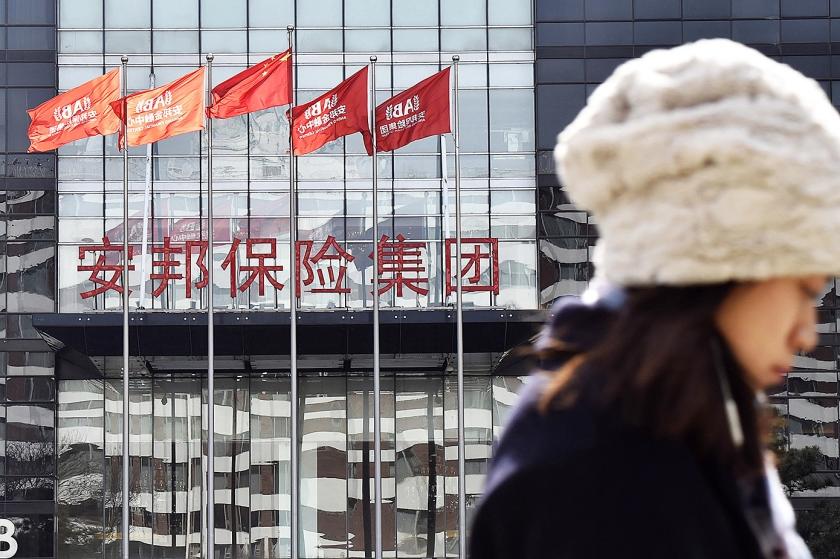 Een vrouw loopt in Peking langs een gebouw van Anbang Insurance Group, die voor minimaal een jaar lang onder Chinese overheidscontrole staat.  (kyodo)