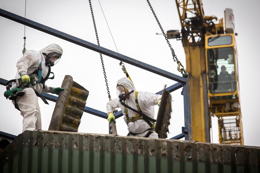 Een asfaltdak wordt van een schuur verwijderd. Particulieren, bedrijven en instellingen mogen vanaf 1 januari 2024 geen asbestdaken meer hebben.  (Harry Cock)