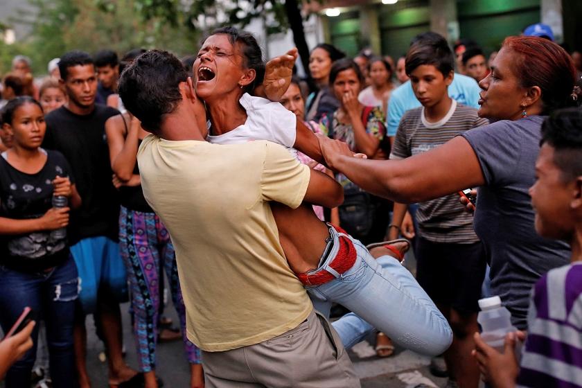 Een familielid van een van de slachtoffers, buiten bij het politiebureau in de Venezolaanse stad Valencia waar na een opstand in het cellenblok de fatale brand ontstond.  (reuters)