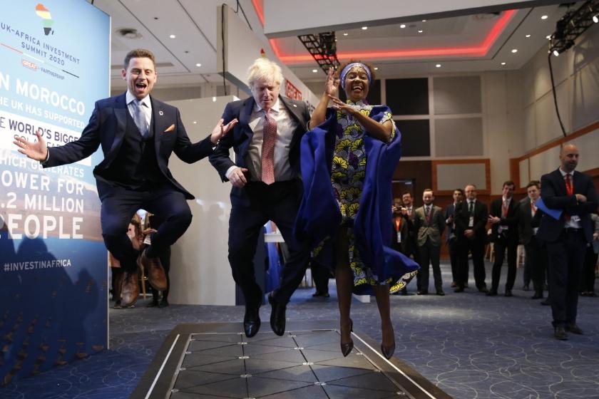 De Britse premier Boris Johnson springt met twee CEO's in de lucht op een innovatiebeurs in Londen. Ze testten een vloer die voetstappen omzet in energie.  (beeld  epa / Hollie Adams)