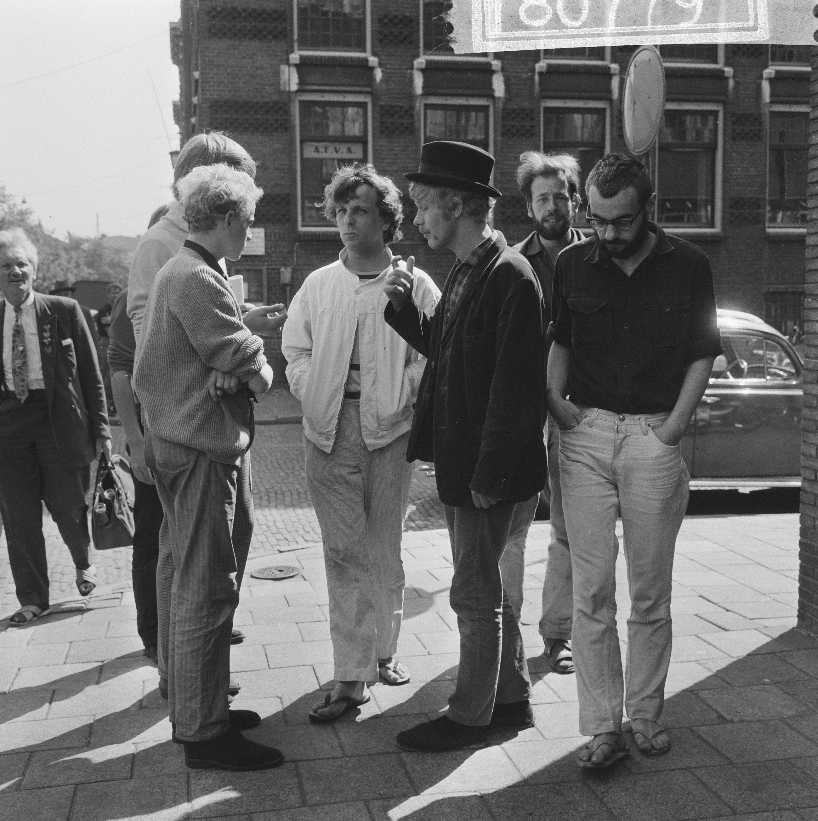 Drie vooraanstaande provo's in Amsterdam, 1965: Robert Jasper Grootveld (in witte jas), Rob Stolk (met hoed) en Roel van Duyn (rechts).