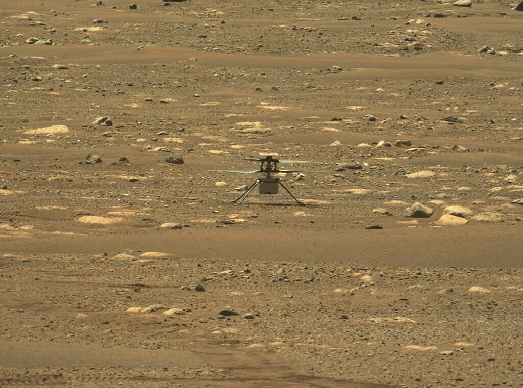 2021-04-19 19:00:37 This NASA photo was taken after the first flight of NASA's Ingenuity Mars Helicopter — and the first powered, controlled flight on another planet,  captured by Mastcam-Z, a pair of zoomable cameras aboard NASA's Perseverance Mars rover, on April 19, 2021. Flying in a controlled manner on Mars is far more difficult than flying on Earth. Mars has significant gravity (about one-third that of Earth's), but its atmosphere is just 1 percent as dense as Earth's at the surface. Stitched together from multiple images, the mosaic is not white balanced; instead, it is displayed in a preliminary calibrated version of a natural color composite, approximately simulating the colors of the scene that we would see if we were there viewing it ourselves. Handout / NASA/JPL-Caltech/MSSS/ASU / AFP  (beeld Captured by Mastcam-z, a Pair of Zoomable Cameras Aboard Nasa's Perseverance Mars Rover, on April 19, 2021. Flying in a Controlled Manner on Mars is far More Difficult Than Flying on Earth. Mars has Significant Gravity (about One-third That of Earth's), but its Atmosphere is Just 1 Percent as Dense as Earth's at the Surface. Stitched Together From Multiple Images, the Mosaic is not White Balanced; Instead, it is Displayed in a Preliminary Calibr)